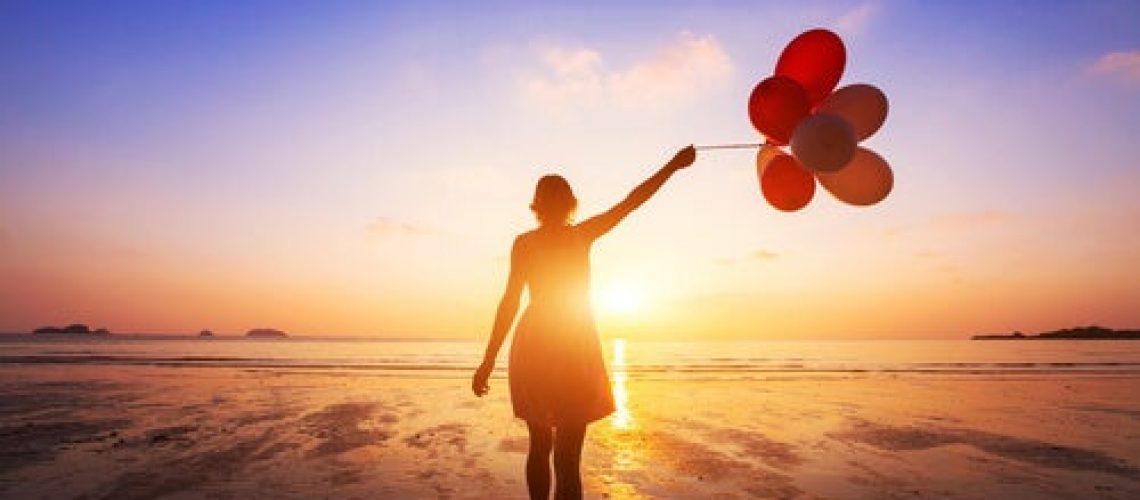 Mujer-con-globos-frente-al-mar